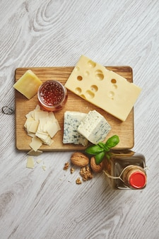 Набор из четырех сыров на деревенской разделочной доске. подается на завтрак с оливковым маслом холодного отжима в винтажной бутылке, деревенским медом и грецкими орехами с листьями базилика.