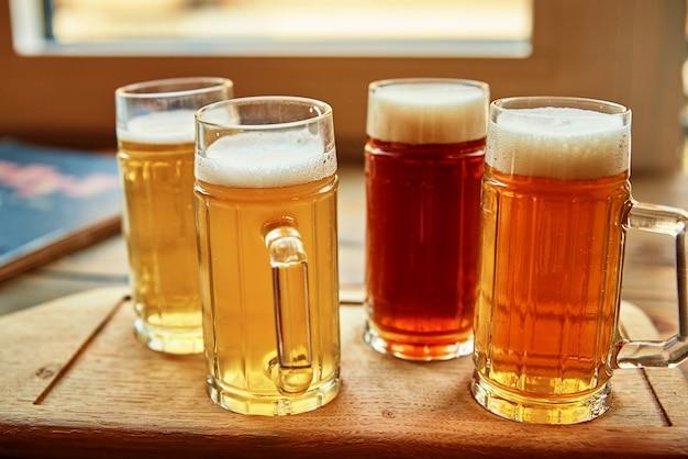 Набор из четырех стаканов с разными сортами пива на столе