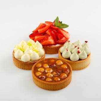 Набор из четырех мини-тарт с ягодами малины, сливками и лесными орехами