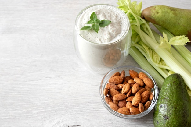 新鮮な緑の野菜のセット:アボカド、セロリ、アーモンド、洋ナシ、テキスト用のスペースのあるテーブルの上の緑のスムージー。