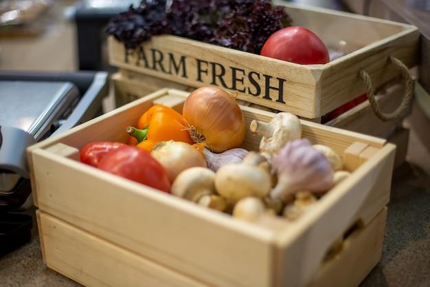 新鮮な有機野菜のニンニク、シャンピニオン、ピーマンのセットは、明るい木製の箱のクローズアップにあります。生物学、バイオ製品、バイオエコロジーの概念、自分で育てた、菜食主義者、農場、作物