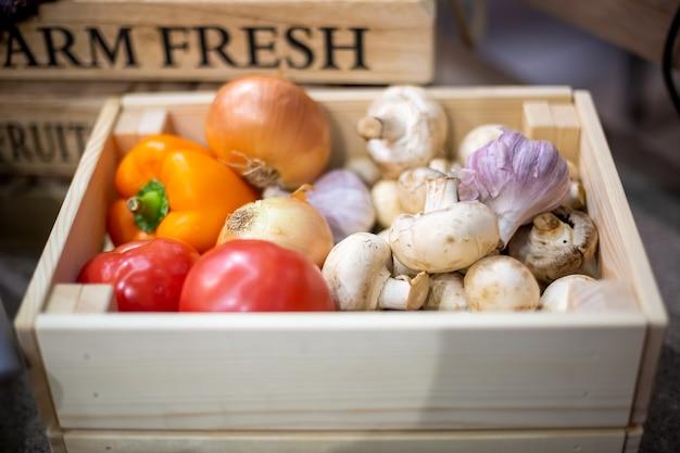 新鮮な有機野菜のニンニク、シャンピニオン、タマネギ、トマト、ピーマンのセットは、明るい木製の箱の中にあります。生物学、バイオ製品、バイオエコロジーの概念、自分で育てた、菜食主義者、農場、作物