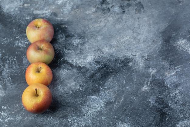 大理石の背景に新鮮な赤いリンゴのセットです。