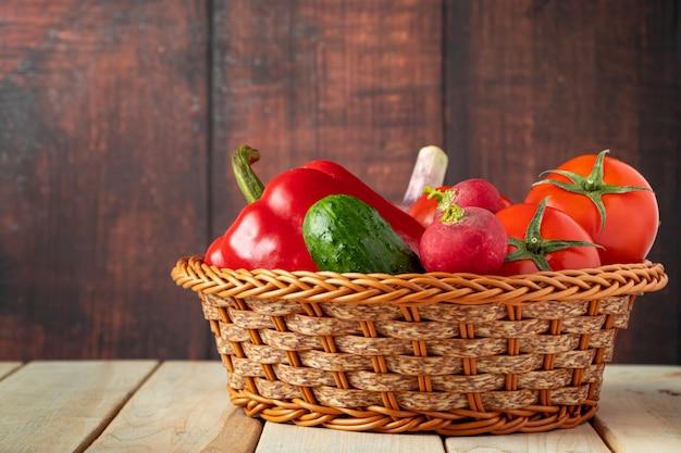 木製の背景上のバスケットに新鮮な野菜のセット。健康的な栄養と食事のコンセプトです。
