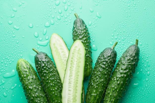 Набор свежих целых и нарезанных огурцов на зеленом фоне с каплями воды. садовый огурец обои фон дизайн