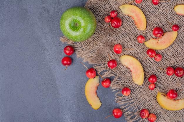 Набор фруктов. яблоко, вишня и дольки персика на синем.