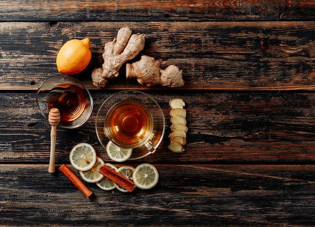 生姜、蜂蜜、乾燥したシナモン、お茶、緑、暗い背景の木のレモンのセット。上面図。テキストのためのスペース