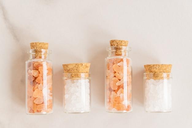 大理石の背景にピンクのヒマラヤと白い海の塩とガラス瓶のセット。