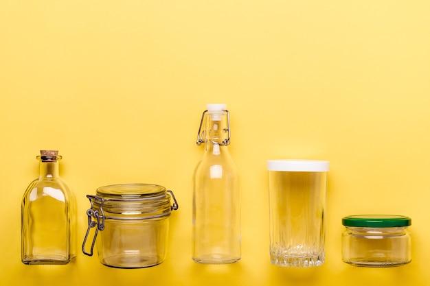 黄色の背景にガラスの瓶とボトルのセット。ゼロプラスチックの概念。