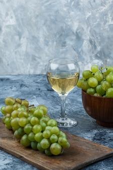 濃い水色の大理石の背景にグラスワイン、まな板のブドウ、ボウルの白ブドウのセット。閉じる。