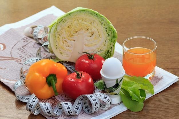 テーブルの上のガラスに新鮮なキャベツ、ピーマン、トマト、卵、マルチビタミンジュースと良い天然物のセット