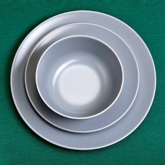 다양한 크기와 모양의 회색 유약 세라믹 접시 세트.