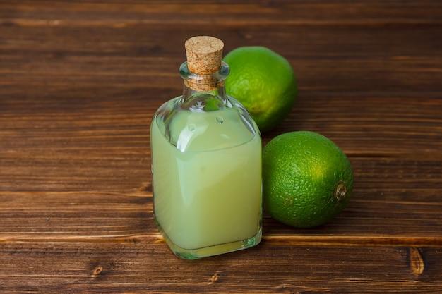 木の表面にグリーンレモンとレモンジュースのセット。ハイアングルビュー。テキスト用のコピースペース
