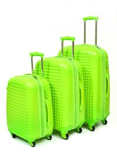 Комплект зеленых чемоданов больших, средних и малых изолированных на белизне.