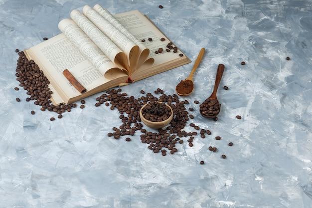 汚れた灰色の背景にボウルと木のスプーンで挽いたコーヒー、本、シナモンスティック、コーヒー豆のセット。ハイアングルビュー。