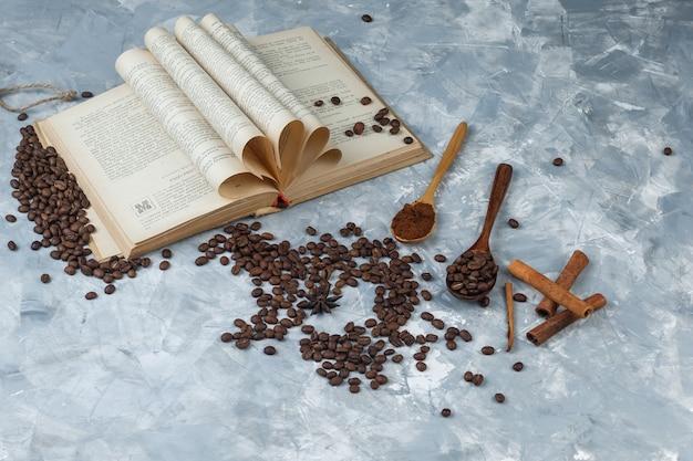 汚れた灰色の背景に木のスプーンで挽いたコーヒー、本、シナモンスティック、コーヒー豆のセット。ハイアングルビュー。