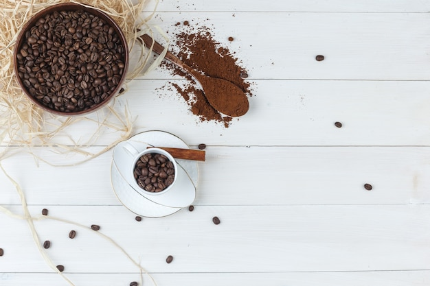 Набор измельченного кофе, палочки корицы и кофейных зерен в миске и чашке на деревянном фоне. вид сверху.