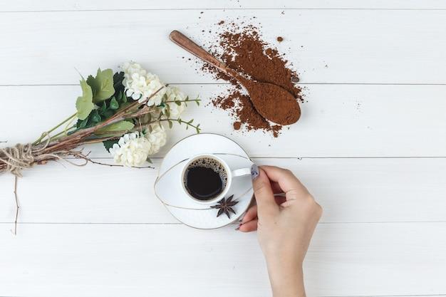 挽いたコーヒー、花、スパイス、木製の背景にコーヒーを持っている女性の手のセットです。フラットレイ。