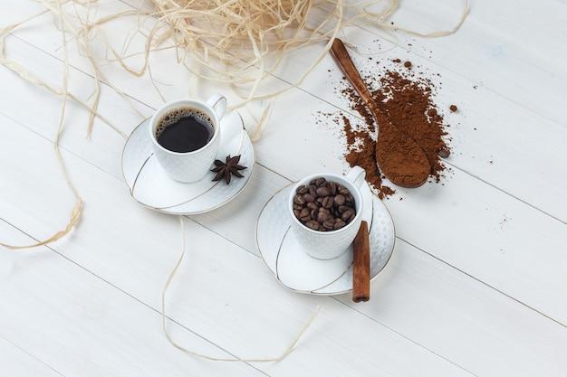 挽いたコーヒー、スパイス、コーヒー豆、木製の背景の上のカップのコーヒーのセットです。ハイアングルビュー。