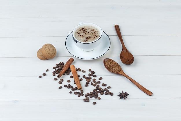 挽いたコーヒー、スパイス、コーヒー豆、クッキー、木製の背景の上のカップのコーヒーのセットです。ハイアングルビュー。
