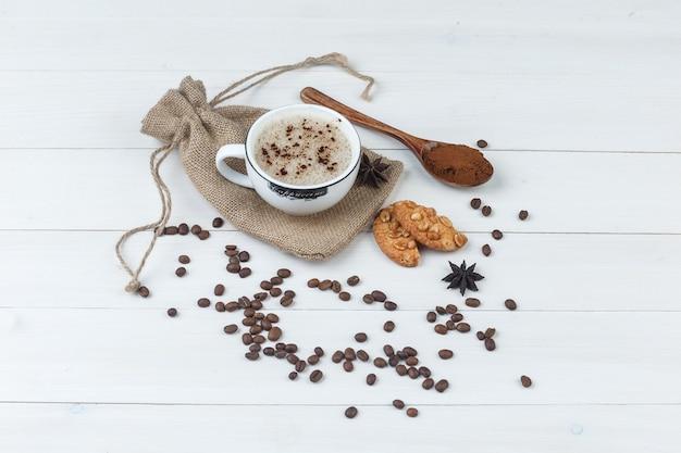 挽いたコーヒー、スパイス、コーヒー豆、クッキー、コーヒーのセットは、木製と袋の背景にカップで。ハイアングルビュー。
