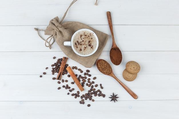 挽いたコーヒー、スパイス、コーヒー豆、クッキー、コーヒーのセットは、木製と袋の背景にカップで。上面図。