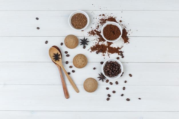 挽いたコーヒー、スパイス、クッキー、木のスプーン、木製の背景のボウルにコーヒー豆のセット。上面図。