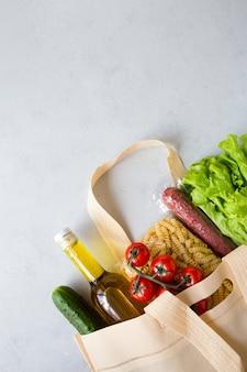 Набор продуктовых предметов в авоське из макарон, масла, салата, помидоров, колбасы плоский лежал на сером с копией пространства.