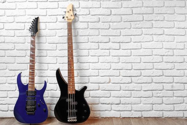 Набор гитар на полу против белой кирпичной стены