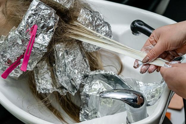 머리 염색 공정 세트. 스타일리스트는 모델 머리카락에서 호일을 벗고 있습니다. 표백 개념