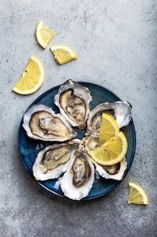 灰色の石の背景、クローズアップ、上面図の素朴な青いプレートにレモンのくさびを添えてシェルで半ダースの新鮮な開いたカキのセット