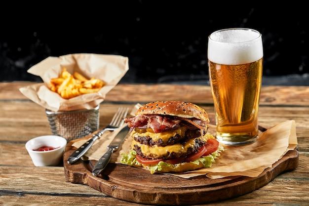 ハンバーガービールとフライドポテトのセットです。パブ、ビール、軽食の飲み物と食べ物の標準セット。暗い背景、ファーストフード。伝統的なアメリカ料理。