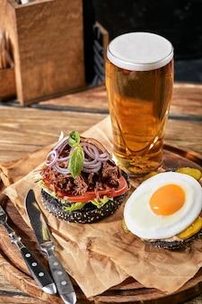 卵とビールのハンバーガーのセットです。パブ、ビール、軽食の飲み物と食べ物の標準セット。暗い背景、ファーストフード。伝統的なアメリカ料理。