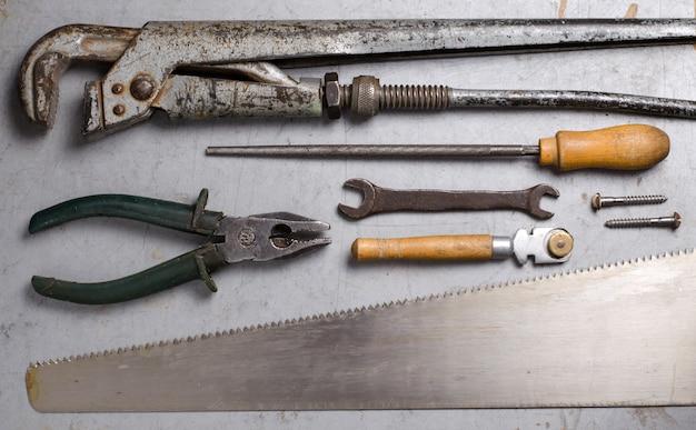 灰色の背景上の手の古いツールのセット