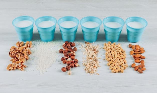 ヘーゼルナッツ、アーモンド、いくつかのナッツと白い木製の背景にミルクのカップのセット。ハイアングル。