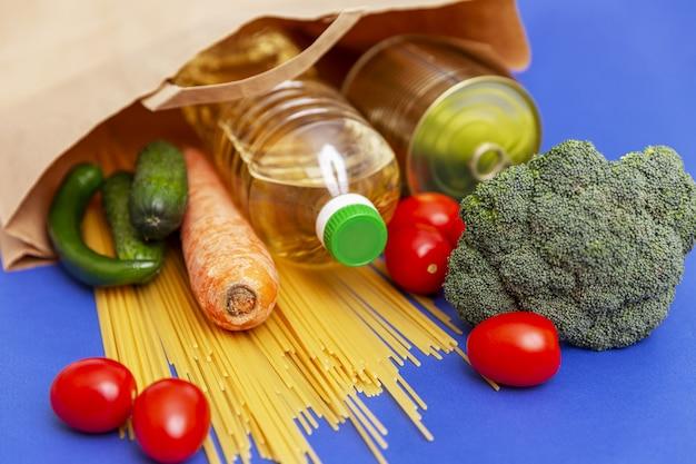 青色の背景に環境に優しい紙袋に健康的な製品のセット。閉じる。スパゲッティ、新鮮な野菜、植物油のボトル。