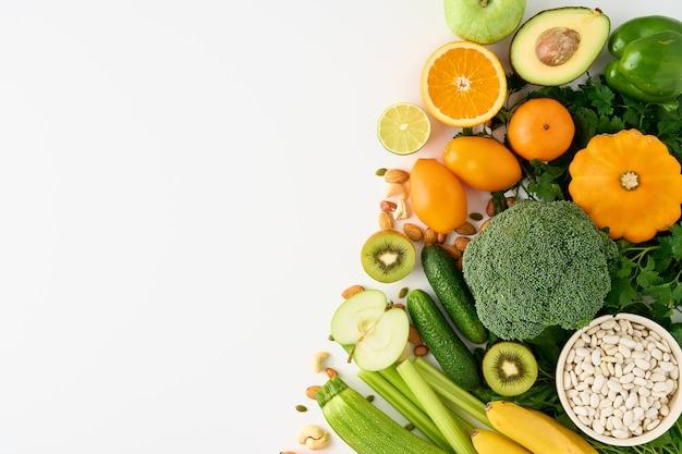 白い背景の上の健康的なビーガン食品カラフルな野菜果物とナッツのセット