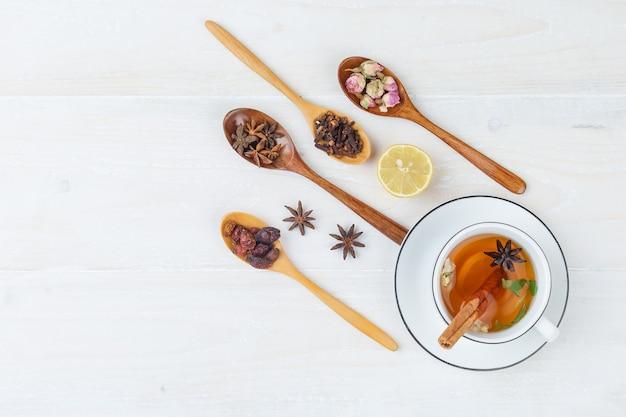 Набор трав и специй и травяной чай на белой поверхности
