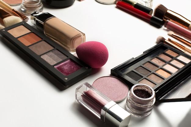 흰색 배경에 형광펜, 핑크 립글로스, 메이크업 팔레트 세트. 텍스트를 위한 공간