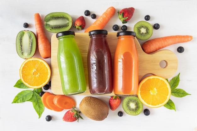 집에서 만든 신선한 과일 주스, 비타민 c 및 보충제의 천연 소스, 유리 병에있는 건강 음료 세트는 흰색 나무 배경에 누워