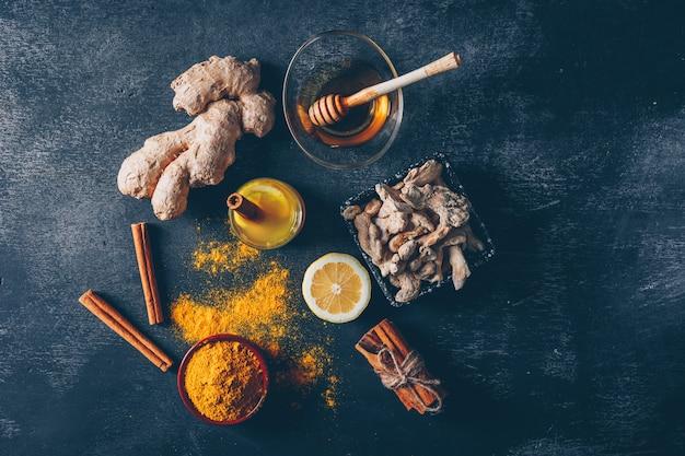 Набор меда, лимона, имбиря и сухой корицы пакет и порошок имбиря в мисках на темном фоне текстурированных. вид сверху.