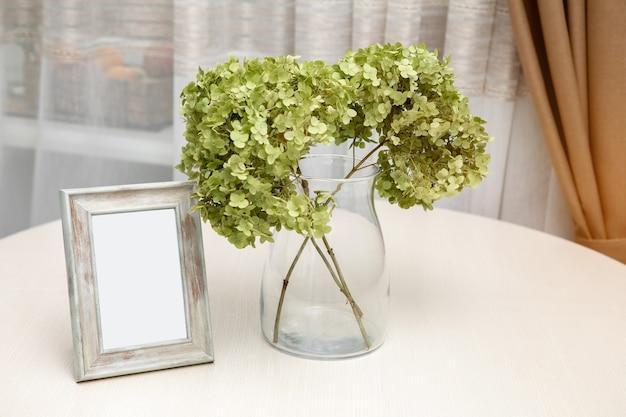 수국 꽃과 흰색 나무 테이블에 빈 사진 프레임 세트