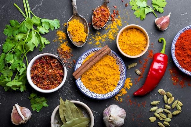 인도 음식 요리 재료 세트. 인도 전통 향신료와 허브. 카레, 강황, 카다멈, 마늘, 후추, 고수, 계피. 이국적인 식사를 준비합니다. 상위 뷰, 클로즈업
