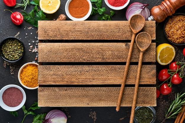 Набор индийских ароматных специй и трав на черном фоне камня. куркума, укроп, перец, корица, шафран, базилик и розмарин по ложке. вид сверху. макет.