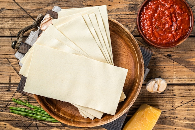 토마토 소스, 파스타, 치즈의 클로즈업 라자냐 요리를 위한 재료 세트. 나무 배경입니다. 평면도.
