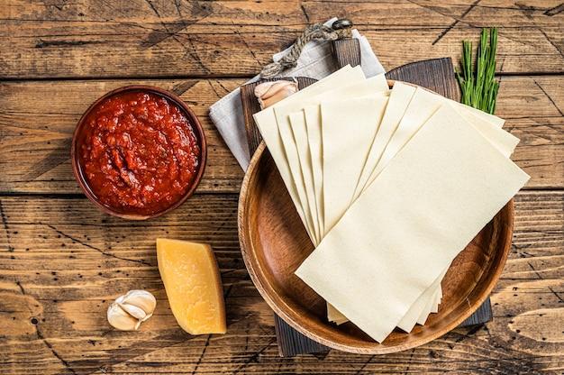 トマトソース、パスタ、チーズのラザニアのクローズアップを調理するための材料のセット。木製の背景。上面図。