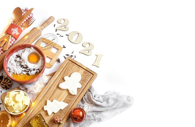 Набор ингредиентов для приготовления праздничного десертного вида сверху на белом фоне с деревянным номером на предстоящий год.