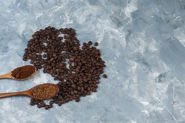 水色の大理石の背景に木のスプーンとコーヒー豆のインスタントコーヒーとコーヒー粉のセット。閉じる。