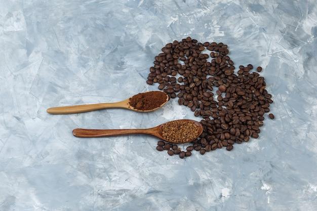 水色の大理石の背景に木のスプーンとコーヒー豆のインスタントコーヒーとコーヒー粉のセット。上面図。