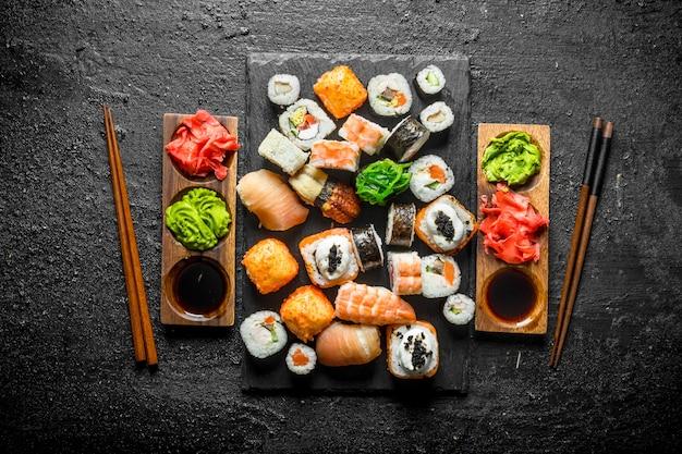 Набор японских суши-роллов на двоих с соусами и палочками. на черном деревенском фоне